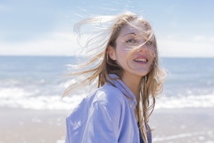 Portrait of smiling young woman with blowing hair at seasideの写真素材 [FYI04335548]