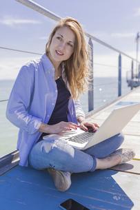 Woman using laptop on jettyの写真素材 [FYI04335553]