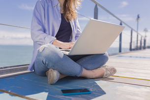 Young woman with laptop and smartphone, sitting on jettyの写真素材 [FYI04335556]