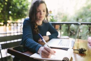 Young woman sitting on balcony using laptopの写真素材 [FYI04335559]