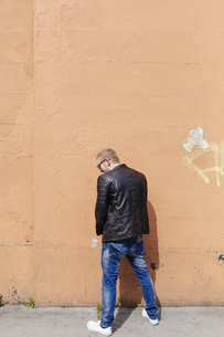 Back view of young man peeing at facadeの写真素材 [FYI04335563]
