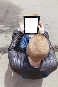 Back view of young man looking at digital tablet, seen fromの写真素材 [FYI04335565]