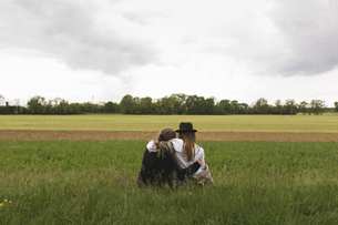 Back view of two friends sitting on a meadow at countrysideの写真素材 [FYI04335567]