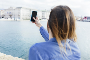 Italy, Trieste, young woman listening taking cell phone pictの写真素材 [FYI04335569]