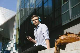 Ireland, Dublin, young businessman sitting on a wall listeniの写真素材 [FYI04335572]