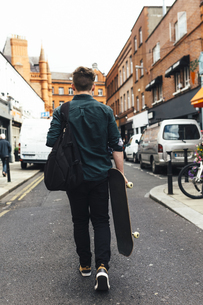 Ireland, Dublin, back view of young man with skateboard walkの写真素材 [FYI04335575]