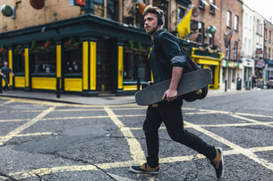 Ireland, Dublin, young man with headphones and skateboard crの写真素材 [FYI04335576]