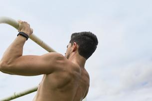 Athlete doing chin-ups outdoorsの写真素材 [FYI04335584]