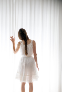 Young woman touching a white curtain, back viewの写真素材 [FYI04335593]