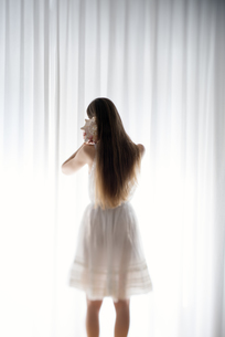 Young woman standing with a shell in front of a white curtaiの写真素材 [FYI04335596]