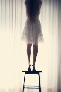 Young woman standing on a stool in front of a white curtain,の写真素材 [FYI04335597]