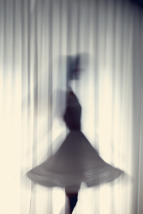 Silhouette of a young woman dancing in front of a white curtの写真素材 [FYI04335598]