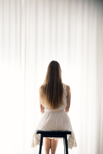 Young woman sitting on a stool in front of a white curtain,の写真素材 [FYI04335600]
