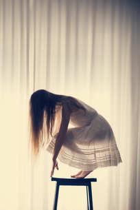 Young woman crouching on a stool in front of a white curtainの写真素材 [FYI04335604]