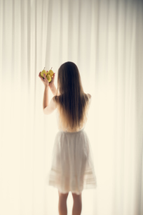 Young woman standing in front of a white curtain holding thrの写真素材 [FYI04335605]
