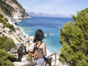 Italy, Sardinia, Gulf of Orosei, Hiker looking at viewの写真素材 [FYI04335697]