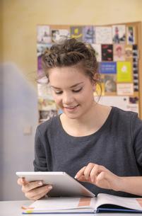 Female pupil using digital tablet while doing homeworkの写真素材 [FYI04335720]