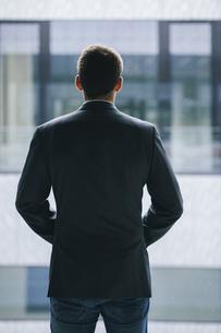 Back view of businessman looking through windowの写真素材 [FYI04335744]