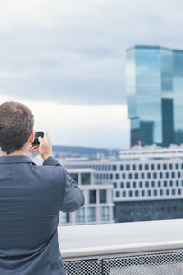 Young man with suit taking photos at business buildingの写真素材 [FYI04335752]