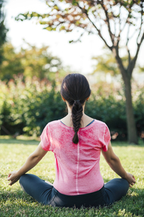 Young woman meditating in parkの写真素材 [FYI04335756]