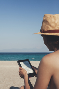Greece, young woman on the beach reading e-bookの写真素材 [FYI04335763]
