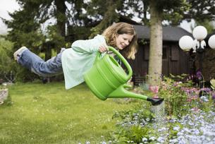 Germany, Bavaria, Kaufbeuren, Mid adult woman watering plantの写真素材 [FYI04335765]