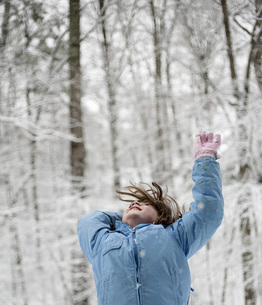 Girl throwing snow in the woodsの写真素材 [FYI04335769]
