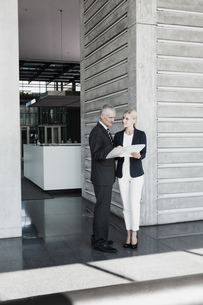 Businessman and businesswoman with documents talking in offiの写真素材 [FYI04335771]