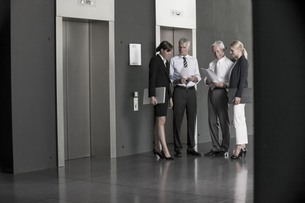 Businesspeople talking at elevatorの写真素材 [FYI04335776]