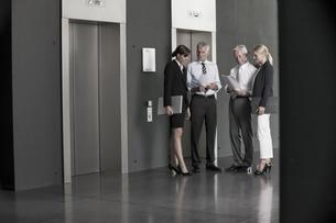 Businesspeople talking at elevatorの写真素材 [FYI04335776]