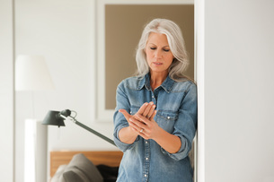 Senior woman with hand pain standing in living roomの写真素材 [FYI04335792]