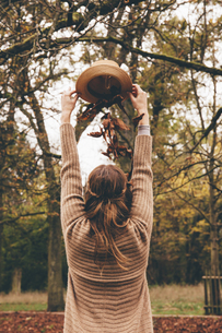 Back view of young woman dropping dried leaves on her head fの写真素材 [FYI04335797]