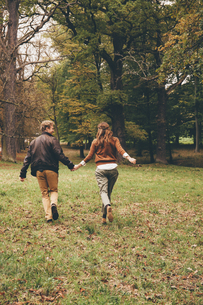 Back view of young couple in love holding hands and runningの写真素材 [FYI04335799]