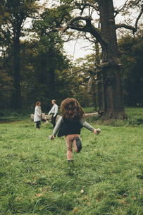 Back view of little girl running in a park while her parentsの写真素材 [FYI04335804]