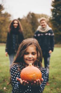 Portrait of smiling little girl showing Hokkaido pumpkin whiの写真素材 [FYI04335805]