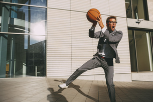 Businessman playing basketball outdoorsの写真素材 [FYI04335807]