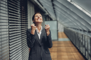 Businesswoman in office building cheering, celebrating succeの写真素材 [FYI04335811]