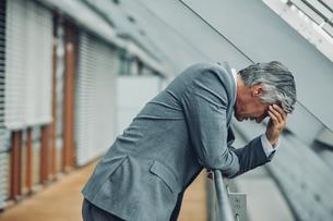 Desperate businessman leaning on railingの写真素材 [FYI04335821]
