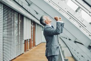 Businessman in office building cheering, celebrating successの写真素材 [FYI04335822]