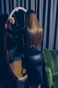 Back view of young woman looking into a mirrorの写真素材 [FYI04335824]