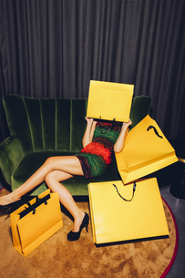 Young woman sitting on couch hiding her face behind a shoppiの写真素材 [FYI04335825]