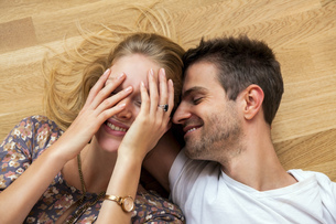 Top view of happy young couple lying on floorの写真素材 [FYI04335828]