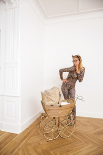 Young woman wearing animal print bodysuit looking at pramの写真素材 [FYI04335831]