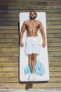 Man lying on sun lounger on deck listening to musicの写真素材 [FYI04335832]