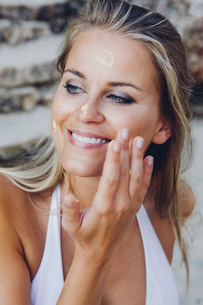 Woman applying sunscreen lotion on her faceの写真素材 [FYI04335835]