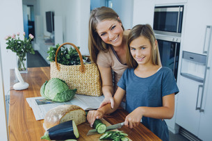 Mother and daughter in kitchen slicing cucumberの写真素材 [FYI04335845]
