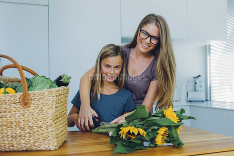 Mother and daughter in kitchen cutting sunflowersの写真素材 [FYI04335846]