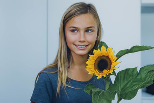 Smiling girl with sunflowerの写真素材 [FYI04335847]