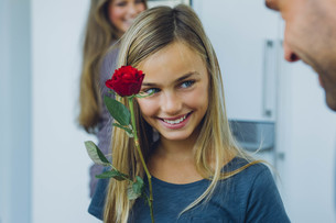 Smiling girl with parents holding roseの写真素材 [FYI04335848]