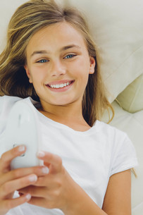 Portrait of smiling girl lying on couchの写真素材 [FYI04335853]